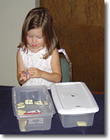 Child working Dominoes, Marbles, and Cards Task